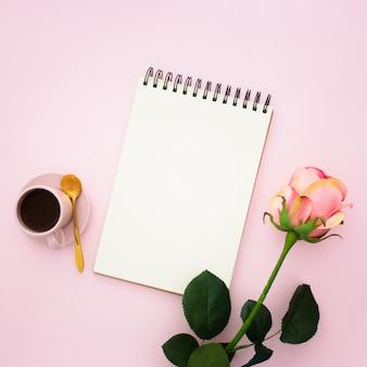 Roze roos, koffie en notitieboekje
