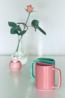 Roze roze bloem en twee halve theemokken in zalmroze en fris mintgroen. minimalistisch design voor uw huis in pastelkleuren. modern interieur, romantische geschenken. wenskaart voor valentijn.