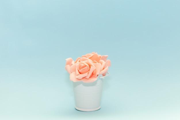 Roze roze bloemblaadjes in een witte speelgoed emmer op een lichtblauwe achtergrond, bloemen voor de vakantie