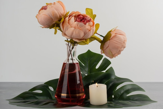 Roze roze bloemen in glasvaas en kaars