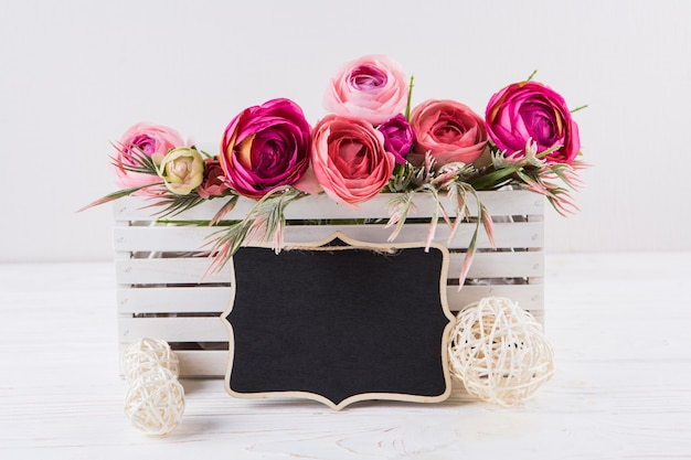 Roze roze bloemen met kleine schoolbord op tafel