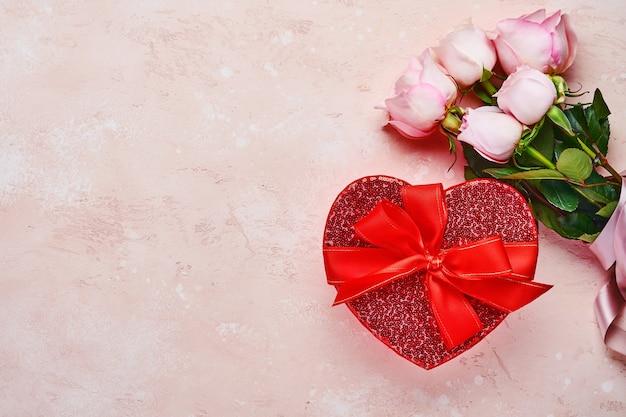 Roze rozen bloemen boeket met lint en rode geschenkdoos die eruit ziet als hart over mooie roze achtergrond. wenskaartsjabloon met kopie ruimte