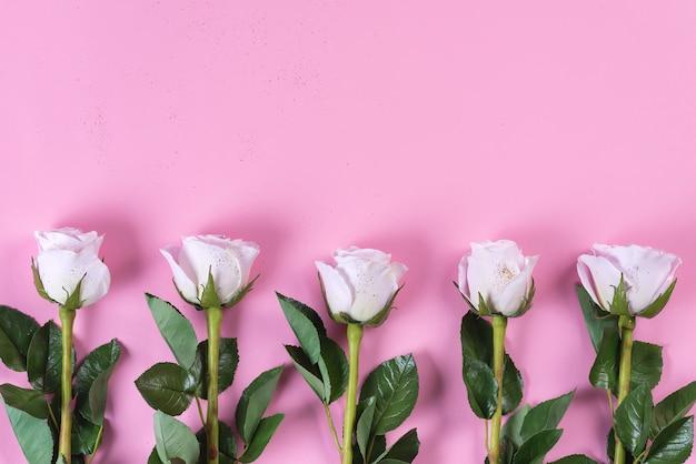 Roze rozen bloemen met gouden glitter op een roze achtergrond, plat lag