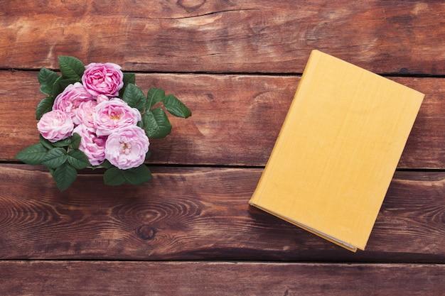 Roze rozen en boek met een gele cover op een houten achtergrond. het concept van romantische verhalen en romans. plat lag, bovenaanzicht