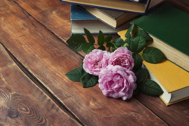 Roze rozen en boek met een gele cover op een houten achtergrond. het concept van romantische verhalen en romans