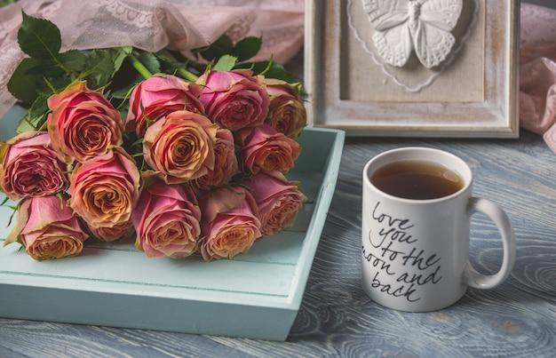 Roze rozen en een witte kop thee met liefdecitaat erop
