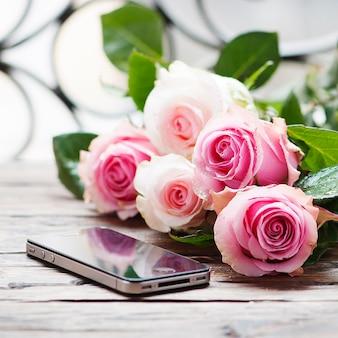 Roze rozen en smartphone op de houten tafel