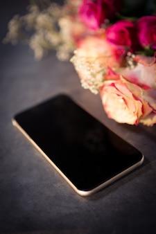 Roze rozen en smartphone op de tafel