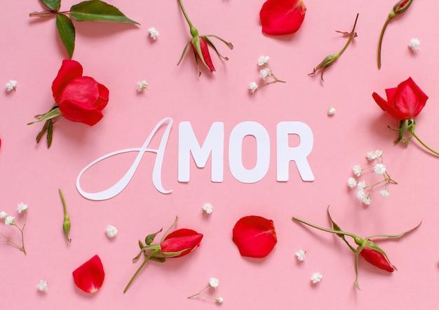 Roze rozen en tekst amor op een lichtroze bovenaanzicht als achtergrond