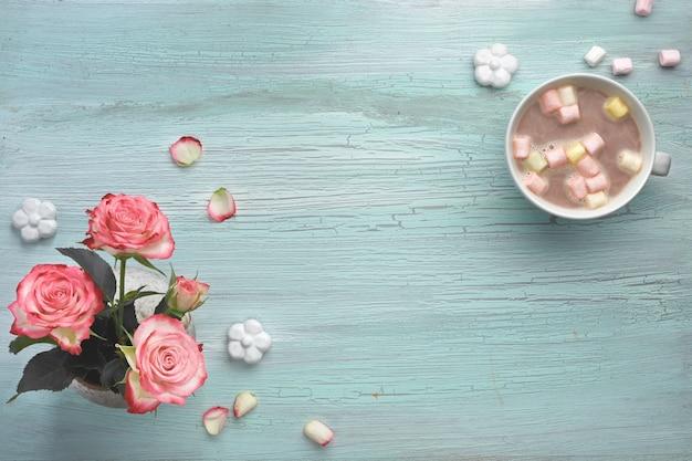Roze rozen en warme chocolademelk op lichte mint met decoratieve keramische bloemen