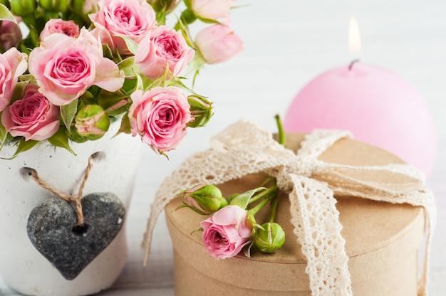 Roze rozen in betonnen pot met kaars