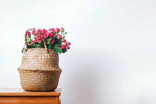 Roze rozen in een rieten mand