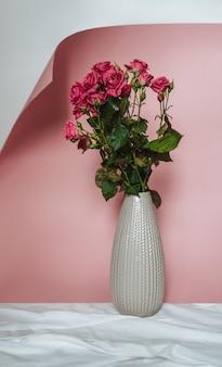 Roze rozen in een vaas op een trendy roze papier