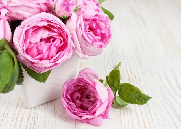 Roze rozen in een vaas op wit houten bureau