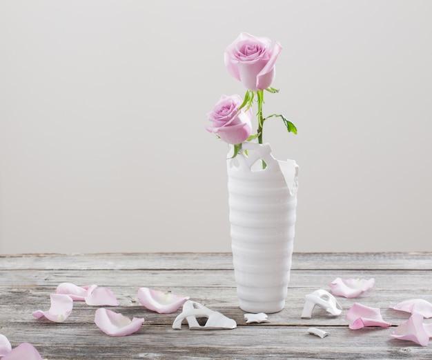 Roze rozen in gebroken bloemenvaas op oude houten tafel
