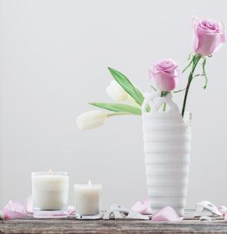 Roze rozen in gebroken vaas en kaars op oude houten tafel
