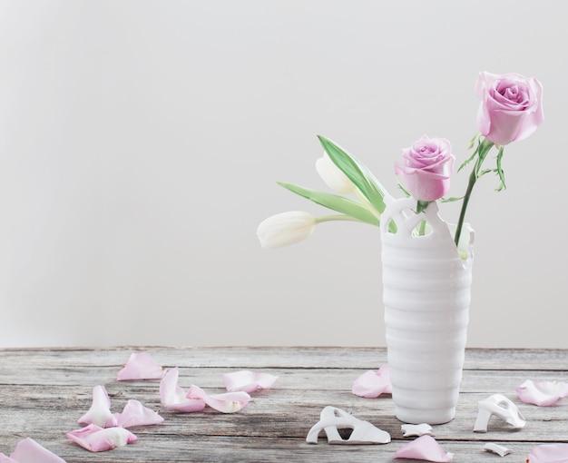 Roze rozen in gebroken vaas op oude houten tafel