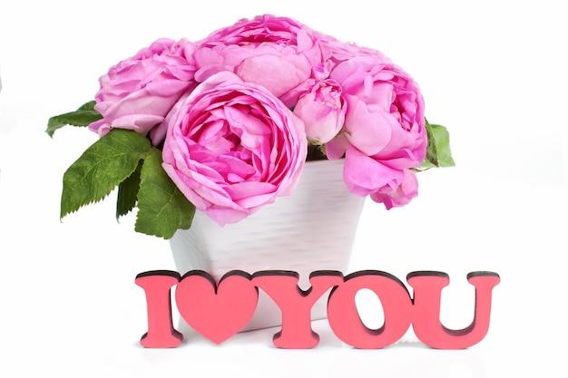 Roze rozen in vaas geïsoleerd op een witte achtergrond en rood houten woord