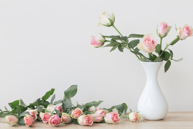 Roze rozen in vaas op witte tafel