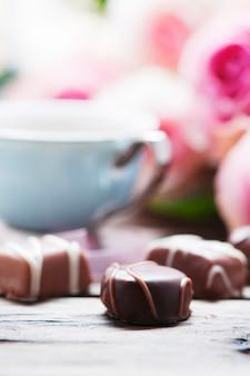 Roze rozen, koffie en chocolade op de houten tafel