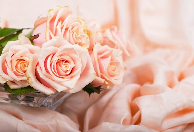Roze rozen met dauwdruppels liggen op een delicaat zijden oppervlak