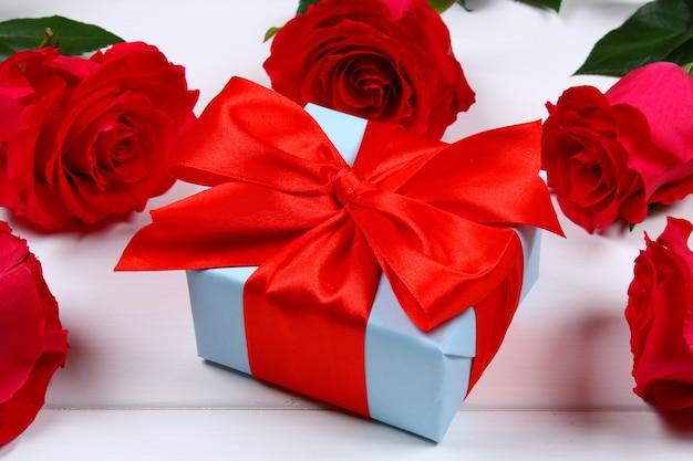 Roze rozen met een geschenkdoos gebonden met een strik.