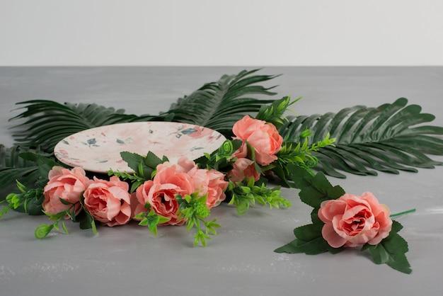 Roze rozen met groene bladeren en plaat op grijze ondergrond.