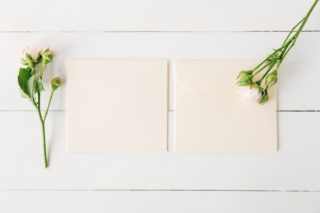 Roze rozen met lege enveloppenminimalistische platte witte houten achtergrond