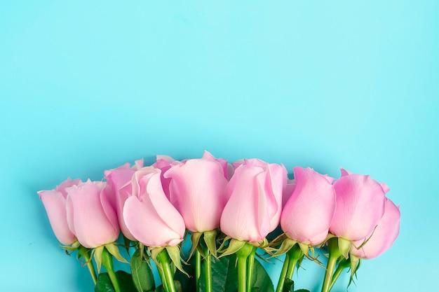 Roze rozen op blauwe achtergrond.