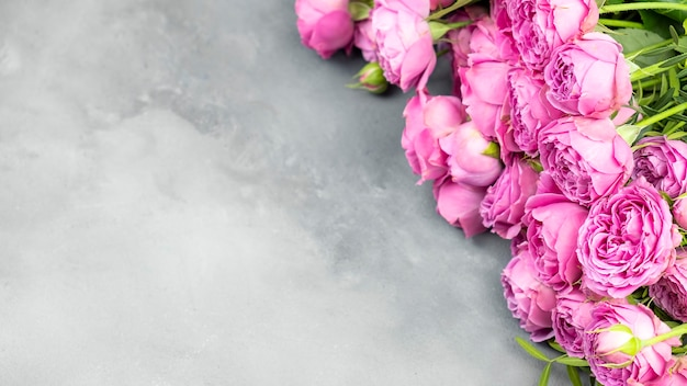 Roze rozen op grijs marmeren tafel, bovenaanzicht