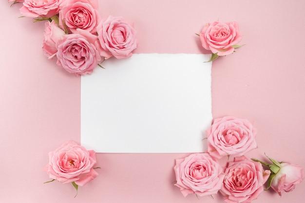 Roze rozen op roze tafel met blanco papier