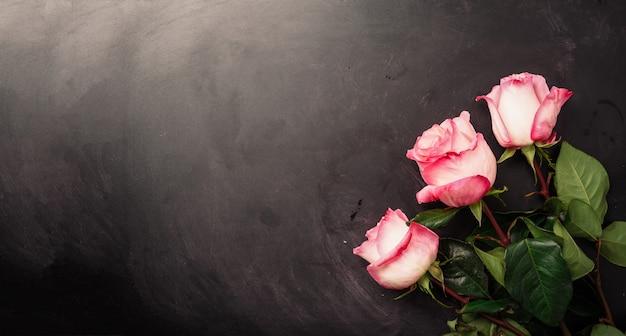 Roze rozen op zwart schoolbord. fijne vrouwendag. valentijnsdag concept. aanwezig voor haar
