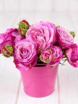 Roze rozen (pioen) in vaas op witte houten tafel. bloemen