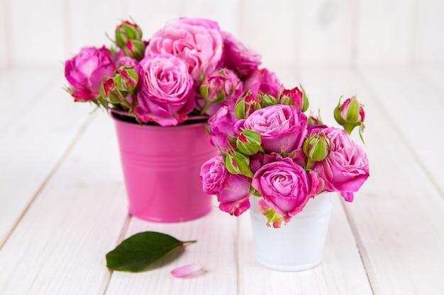 Roze rozen (pioen) in vaas op witte houten.