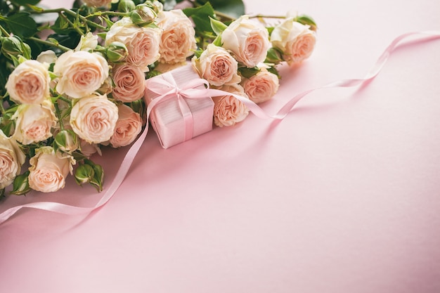 Roze rozenbloemen en gift of huidige doos roze achtergrond. moederdag, verjaardag, valentijnsdag, womens dayconcept.