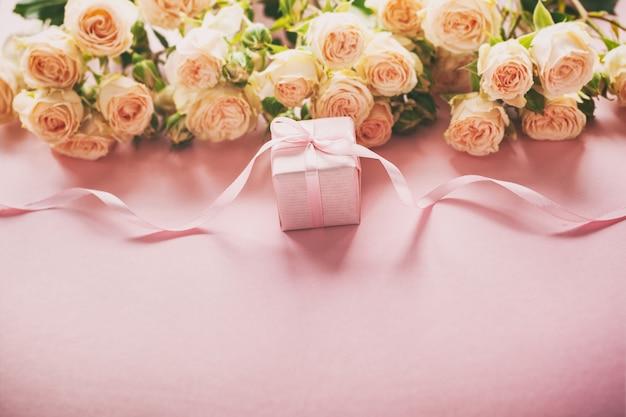 Roze rozenbloemen en gift of huidige doos roze achtergrond.