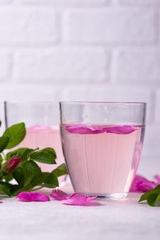 Roze rozenwater met bloemblaadjes en bladeren