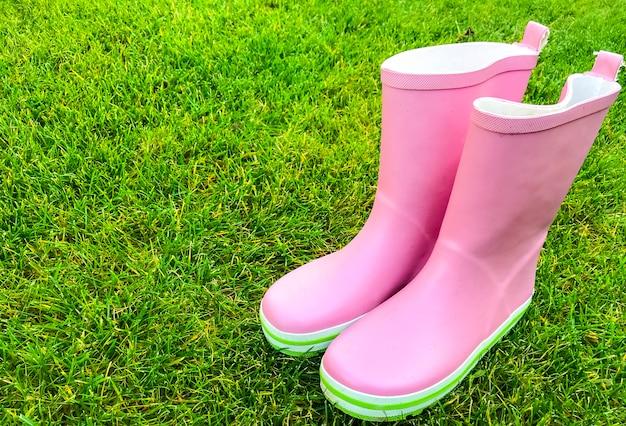 Roze rubberen laarzen staan op groen gras.