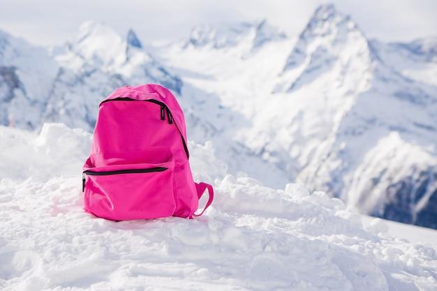Roze rugzak in de van besneeuwde bergen.