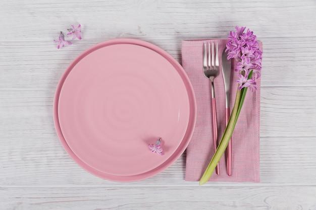 Roze rustieke couvert met paarse hyacintbloem en linnen servet op witte houten oppervlak