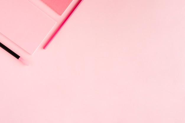 Roze samenstelling met kantoorbehoeften op gekleurde achtergrond