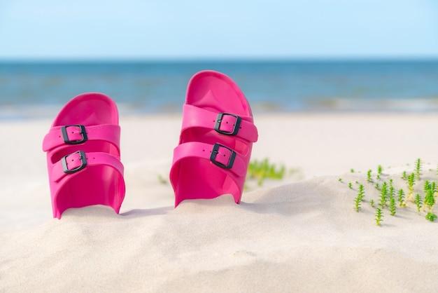 Roze sandalen op het strand op een mooie zonnige dag