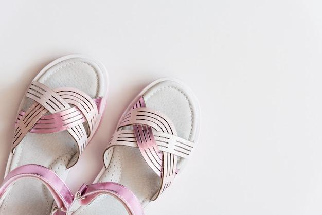 Roze sandals van het babymeisje die op achtergrond worden geïsoleerd. babymode paar roze sandalen schoenen voor de peuters voeten.