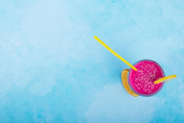 Roze sap in een glazen beker met gele pijpen, bovenaanzicht