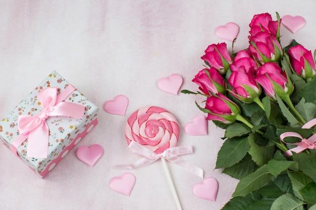Roze satijnen hartjes, snoep, een boeket roze rozen en een cadeau in een doos