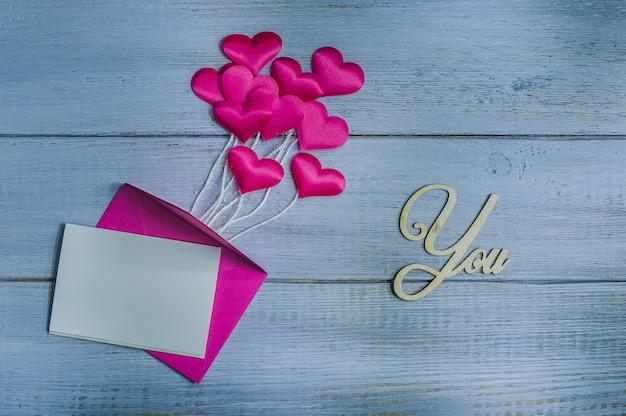 Roze satijnharten boven envelop op houten achtergrond