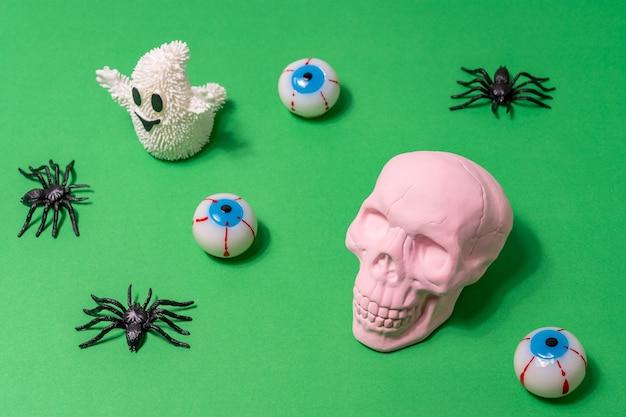 Roze schedel met spinnenoogbollen en witte geest op groene achtergrond Premium Foto