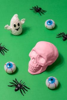 Roze schedel met spinnenoogbollen en witte geest op groene achtergrond