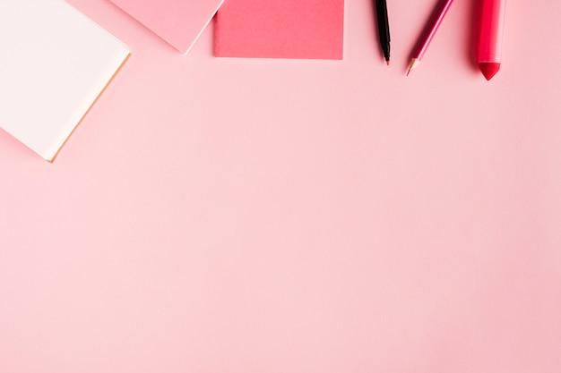 Roze schoolhulpmiddelen op gekleurde oppervlakte