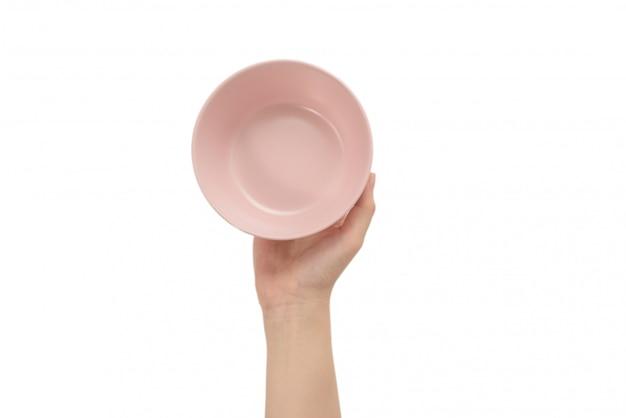 Roze schotel in geïsoleerde vrouwenhanden